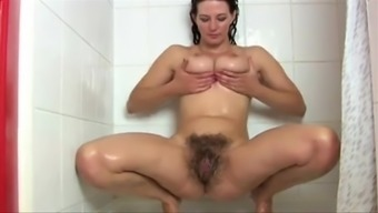 Dark stunner acts together great tits after that two fingers her hairy twat whereas taking a shower